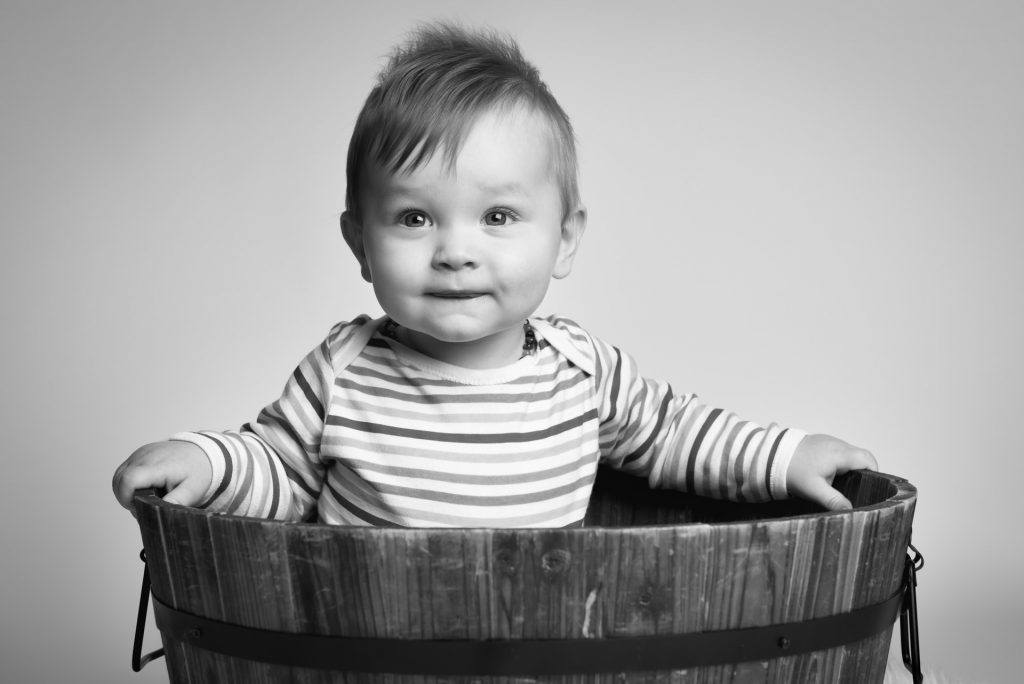beautiful toddler having a photo shoot in a bucket